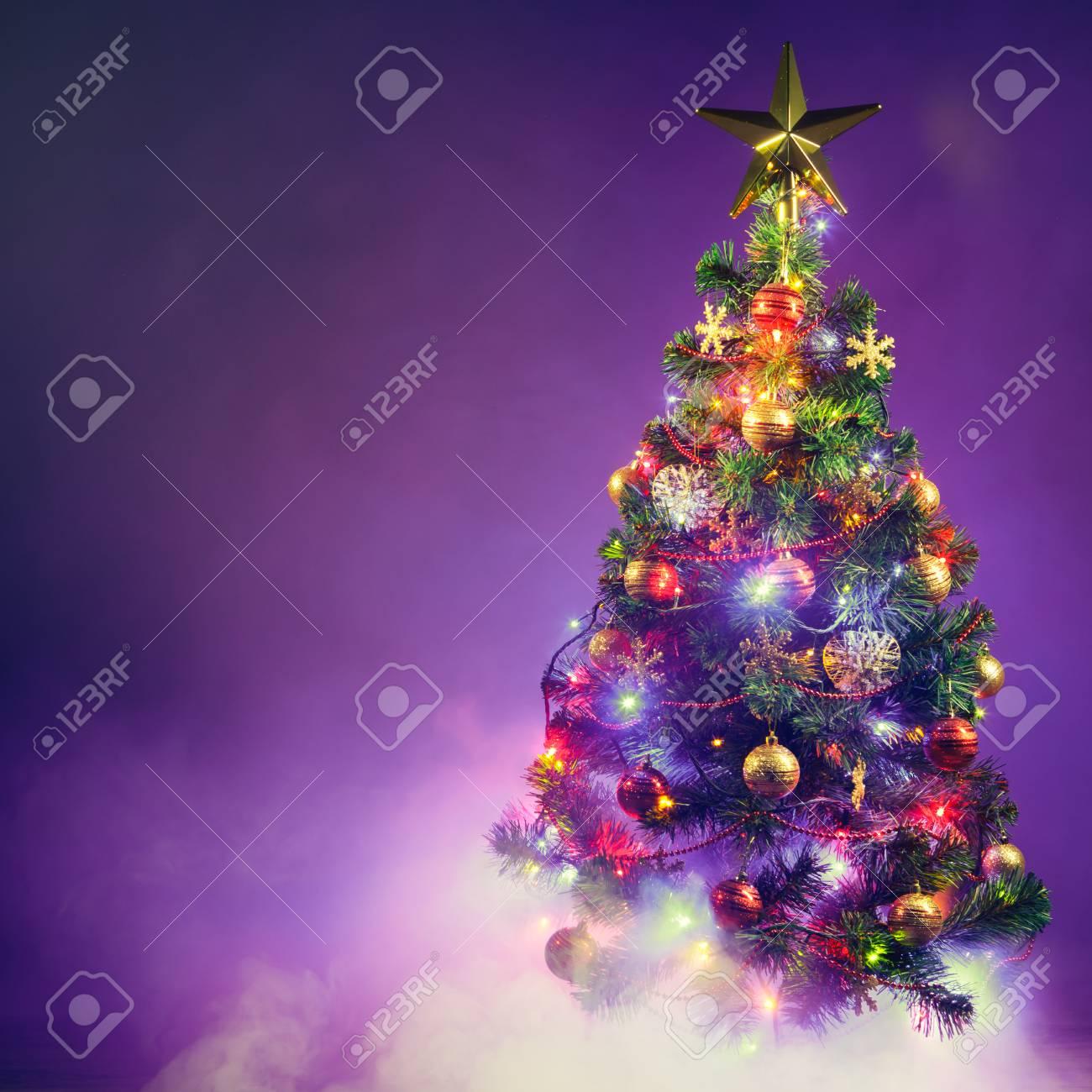 Purple Christmas Tree Lights.Christmas Tree With Festive Lights Purple Background With Smoke