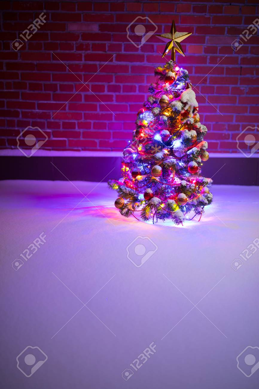 Purple Christmas Tree Lights.Christmas Tree With Festive Lights In Snow Outdoors Purple Brick