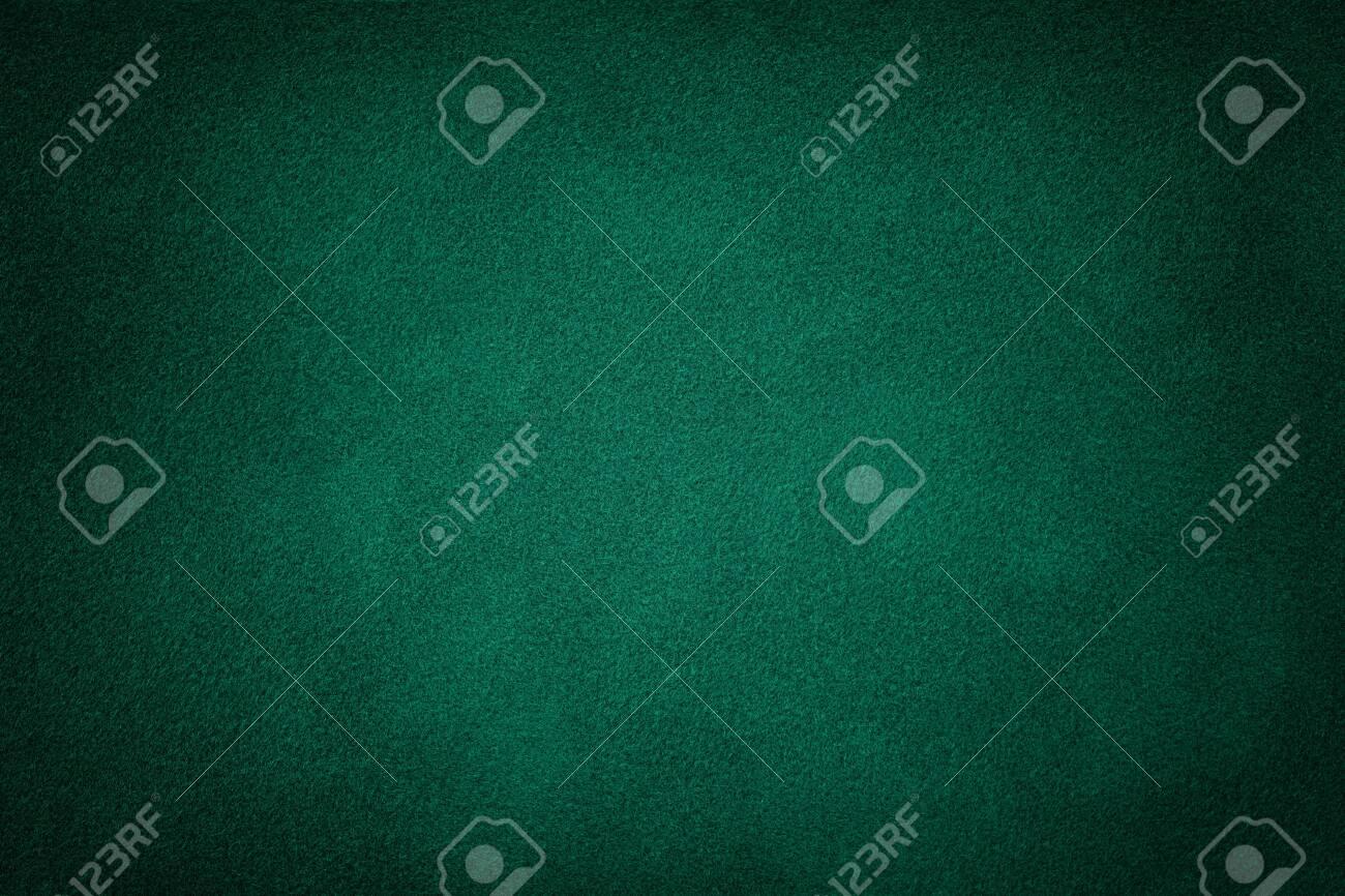 Dark green matte background of suede fabric, closeup. Velvet texture of seamless deep emerald leather. Felt material macro with vignette. - 129690139