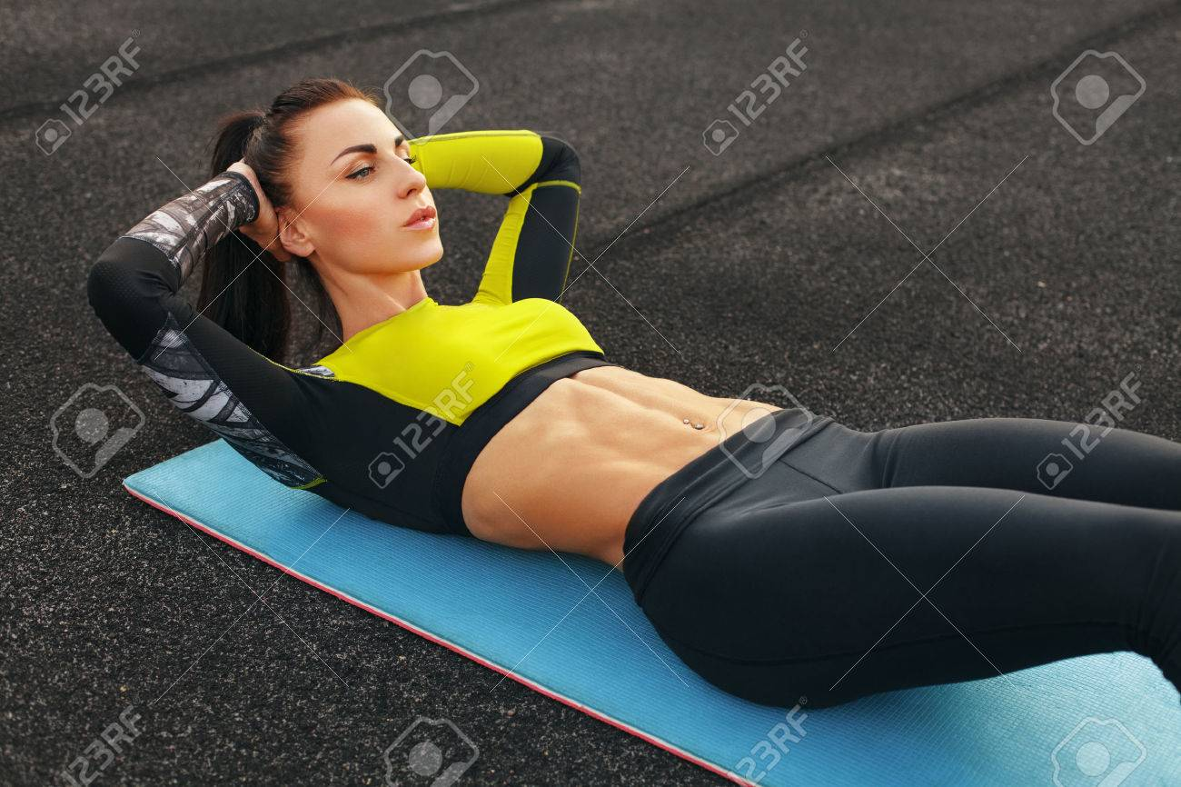 Fitness woman doing sit ups in the stadium working out. Sporty girl exercising abdominals, outdoor - 50827293