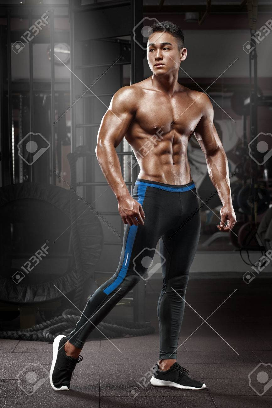 Sexy asian muscular man posing in gym, shaped abdominal. Strong male naked  torso abs
