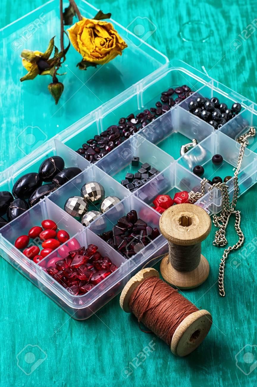 Box mit perlen und faden auf holzuntergrund türkise farbe ...