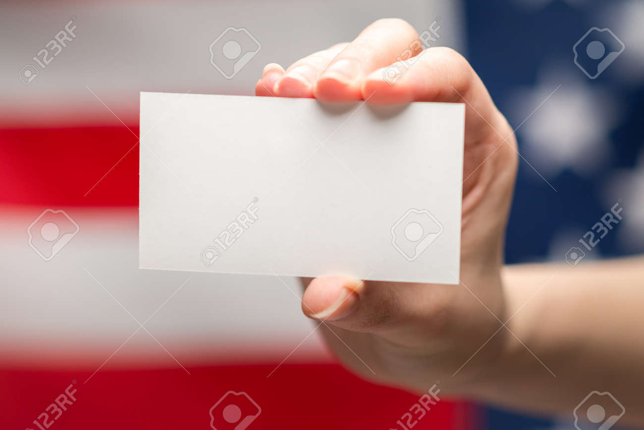 Empty card in woman hand. Copy space. American flag background. - 168845523