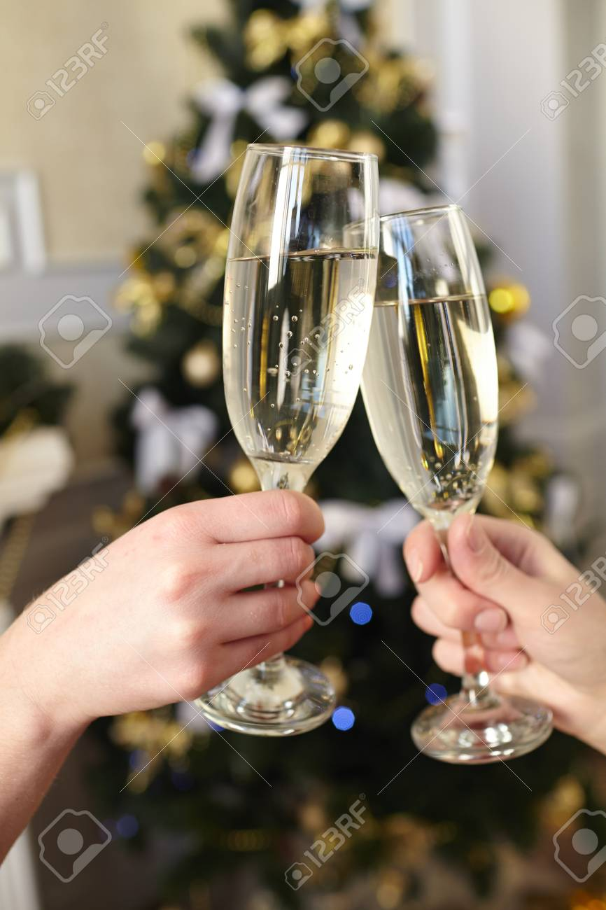Glasses of champagne in female hands on Christmas party - 43954542