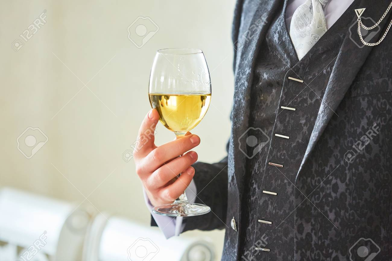 A glass of wine in a man's hand in a retro suit - 82921309