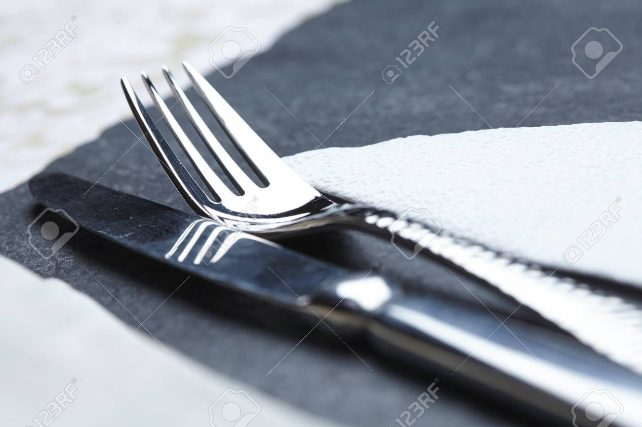 knife and fork on a table a napkin - 82921348