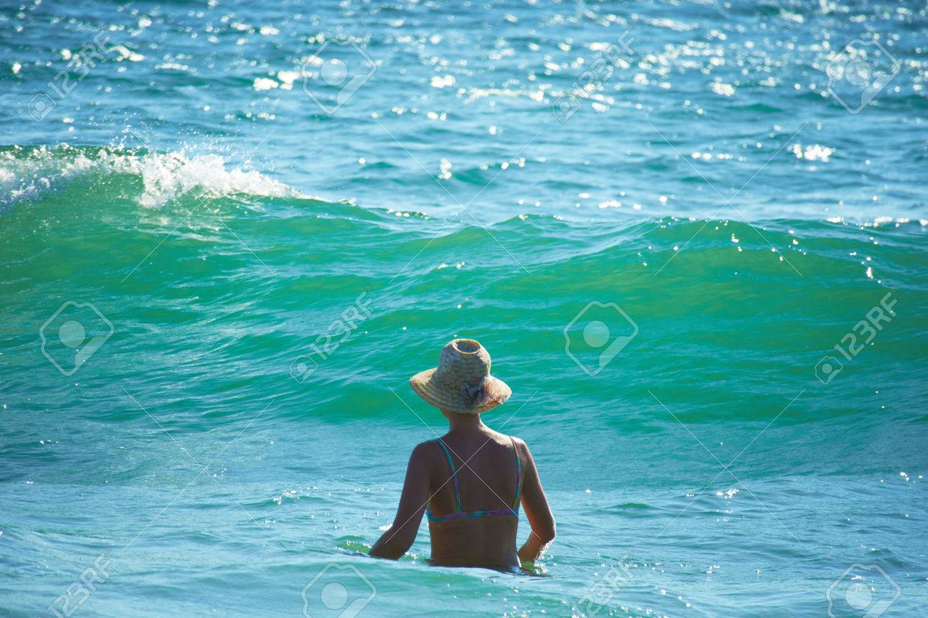 Woman with hat in the sea - 82921837
