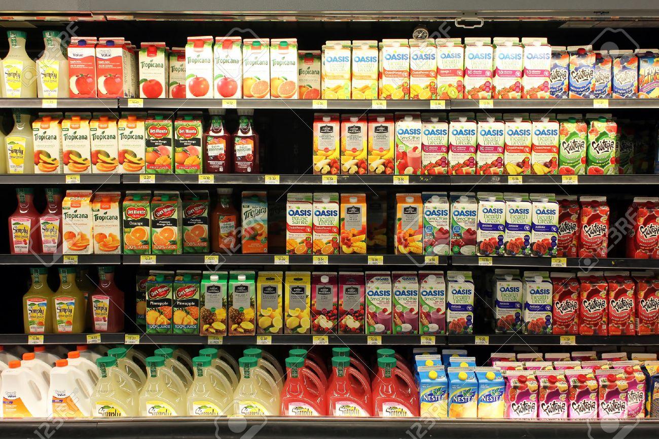 Fruit juices on shelves in a supermarket - 29910704