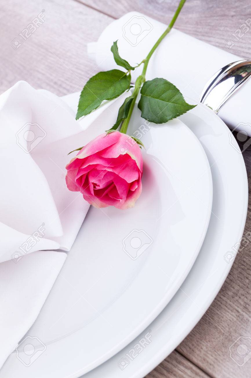 romantic formal elegant table setting with a single pink rose