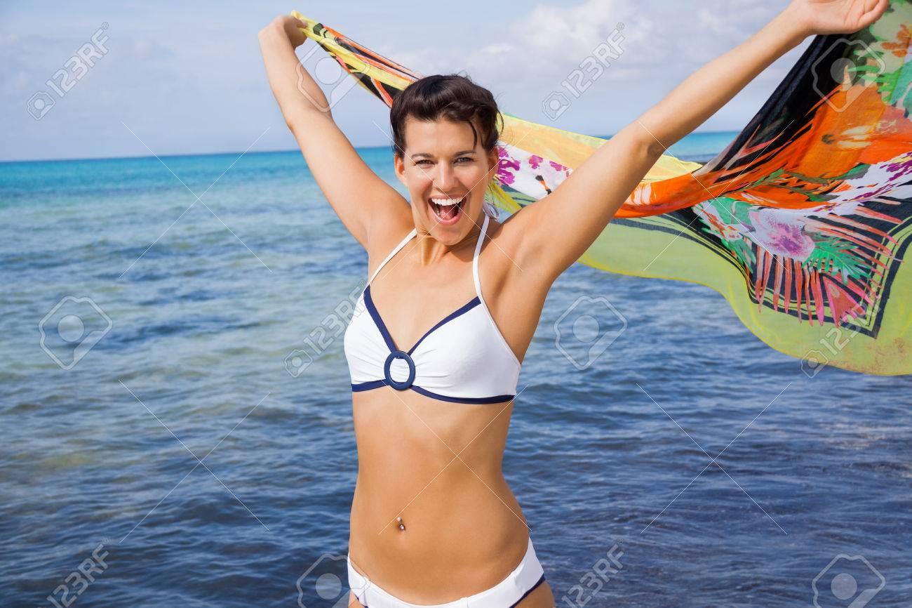 adf6f9963275 Rire femme vive dans un bikini au bord de la mer tenant un foulard à motif  coloré dans ses mains tendues au flottent dans la brise contre une toile de  ...