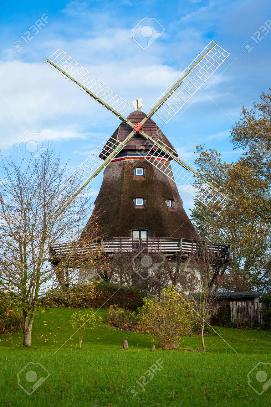 Traditional Wooden Windmill In A Lush Garden With Four Sails Or Blades  Turning In The Wind