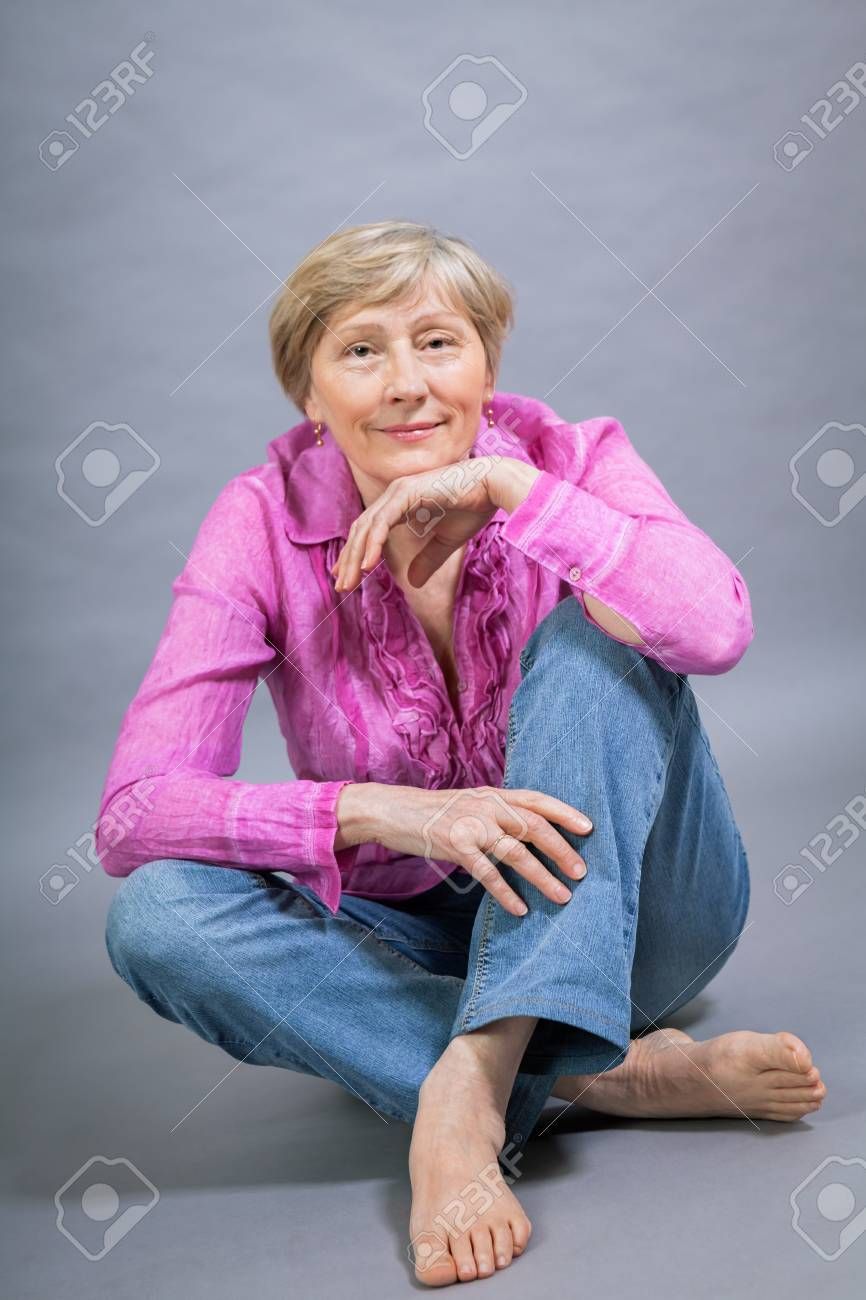 232f6f3a0e968 Beautiful blond trendy senior woman posing in a pink blouse and jeans  sitting on the floor
