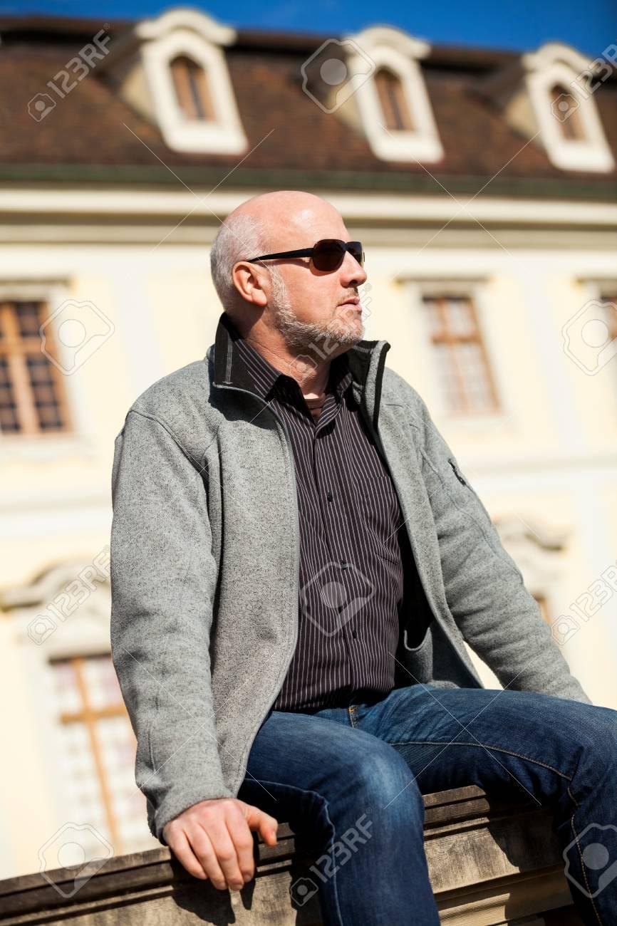 Légant homme d'âge moyen dans des lunettes de soleil profitant du soleil assis en plein air sur un mur de pierre dans un environnement urbain