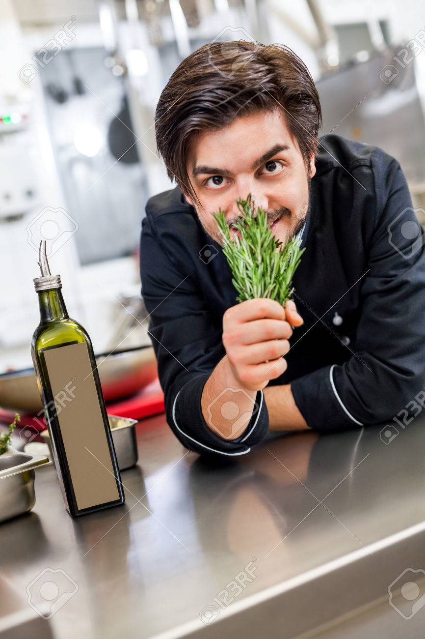 Chefs buying fresh herbs - Chef Checking The Freshness Of A Bunch Of Fresh Herbs By Smelling The Aroma Before Using