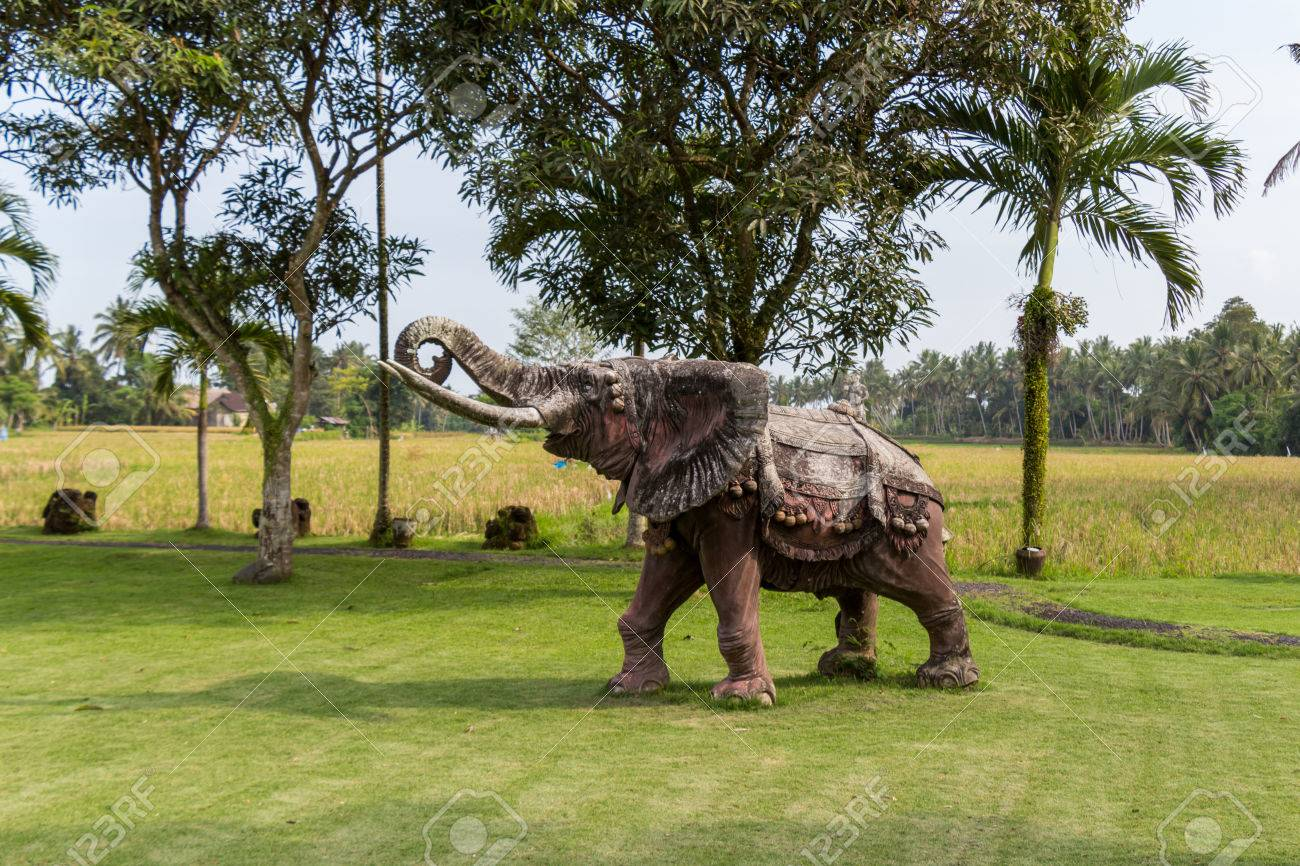 Realistic Naturalistic Elephant Statue Standing On A Lawn At A Park Or  Landscaped Garden In Bali