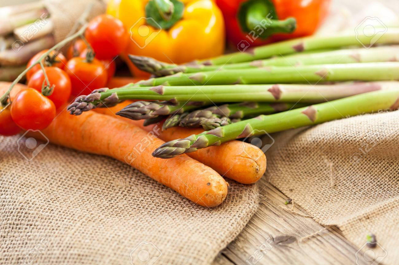Fresh Vegetables In A Country Kitchen With Green Asparagus Spears Cherry Tomatoes On The