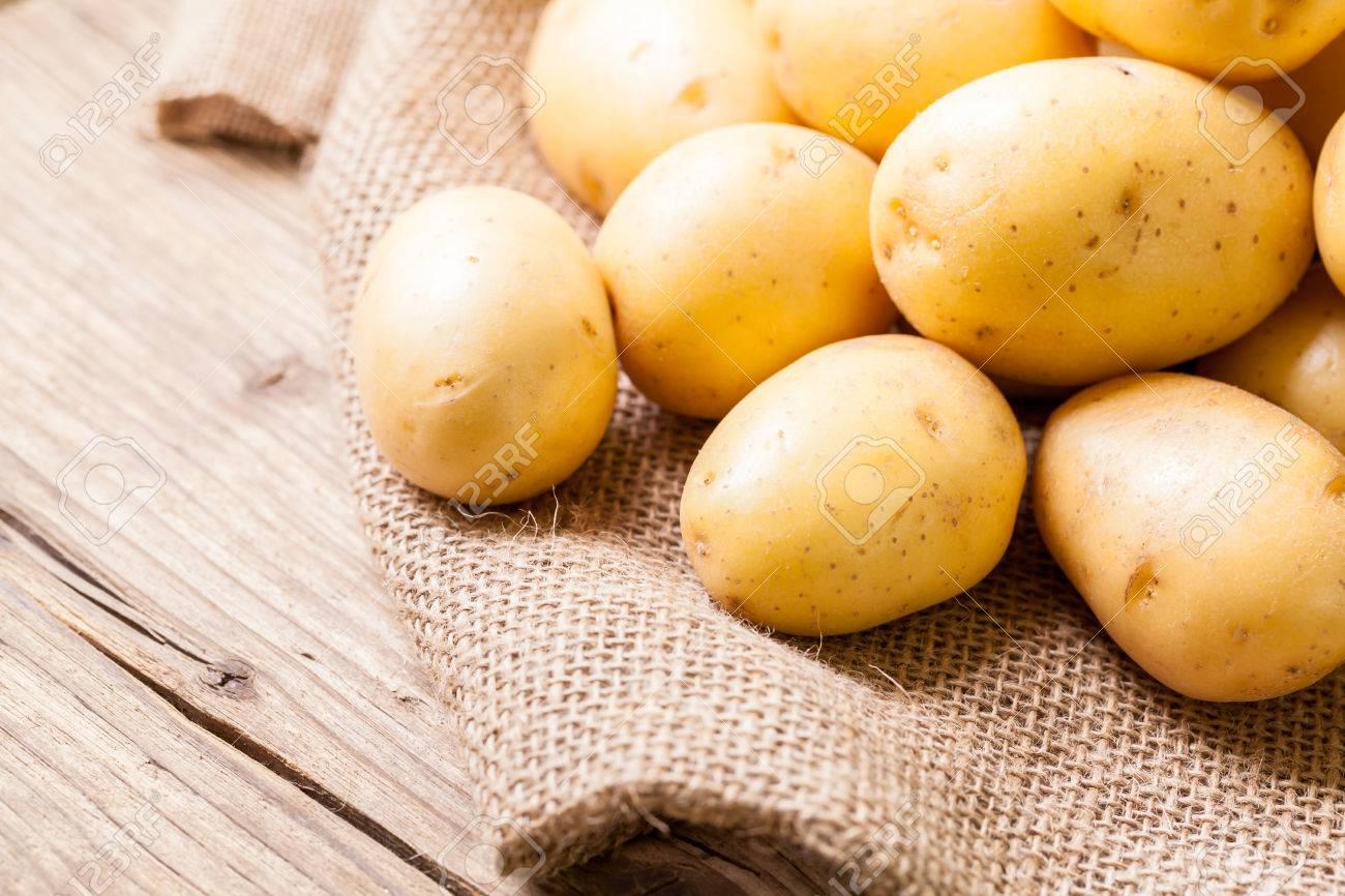 Sac À Patates Toile De Jute ferme petites pommes de terre fraîches affichées sur un sac de toile de  jute sur une table en bois rustique au marché des fermiers, une racine