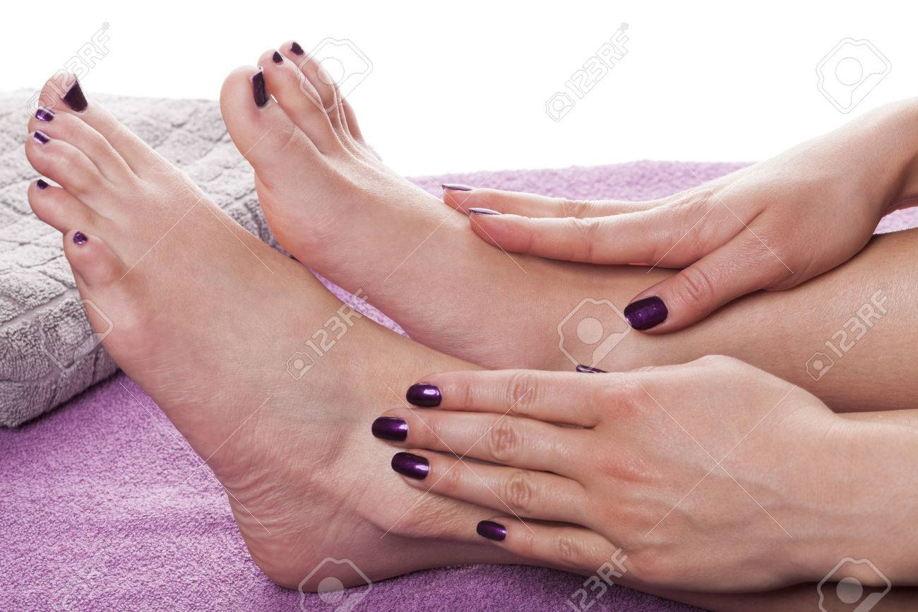 Manicured Hands Stroke Bare Feet Painted With Dark Nail Polish ...