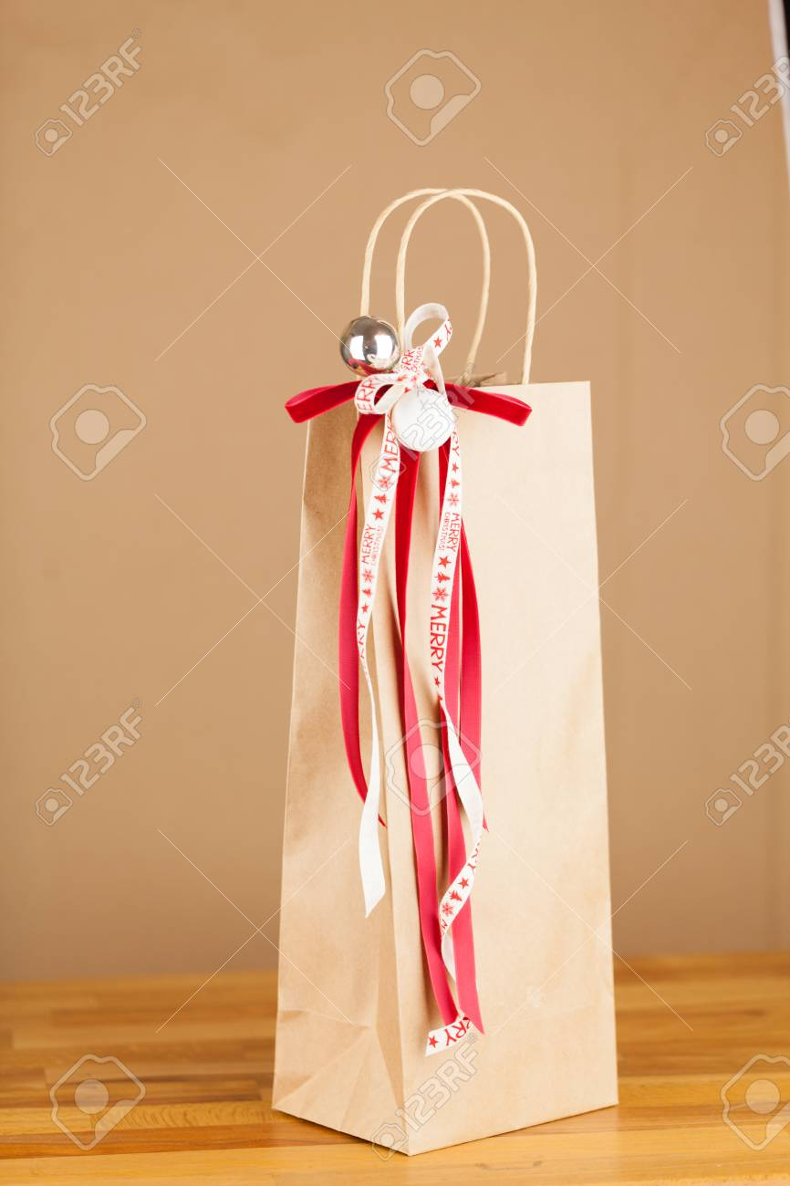 Close Up Of Christmas Gift Bag Of Kraft Paper With Red And White