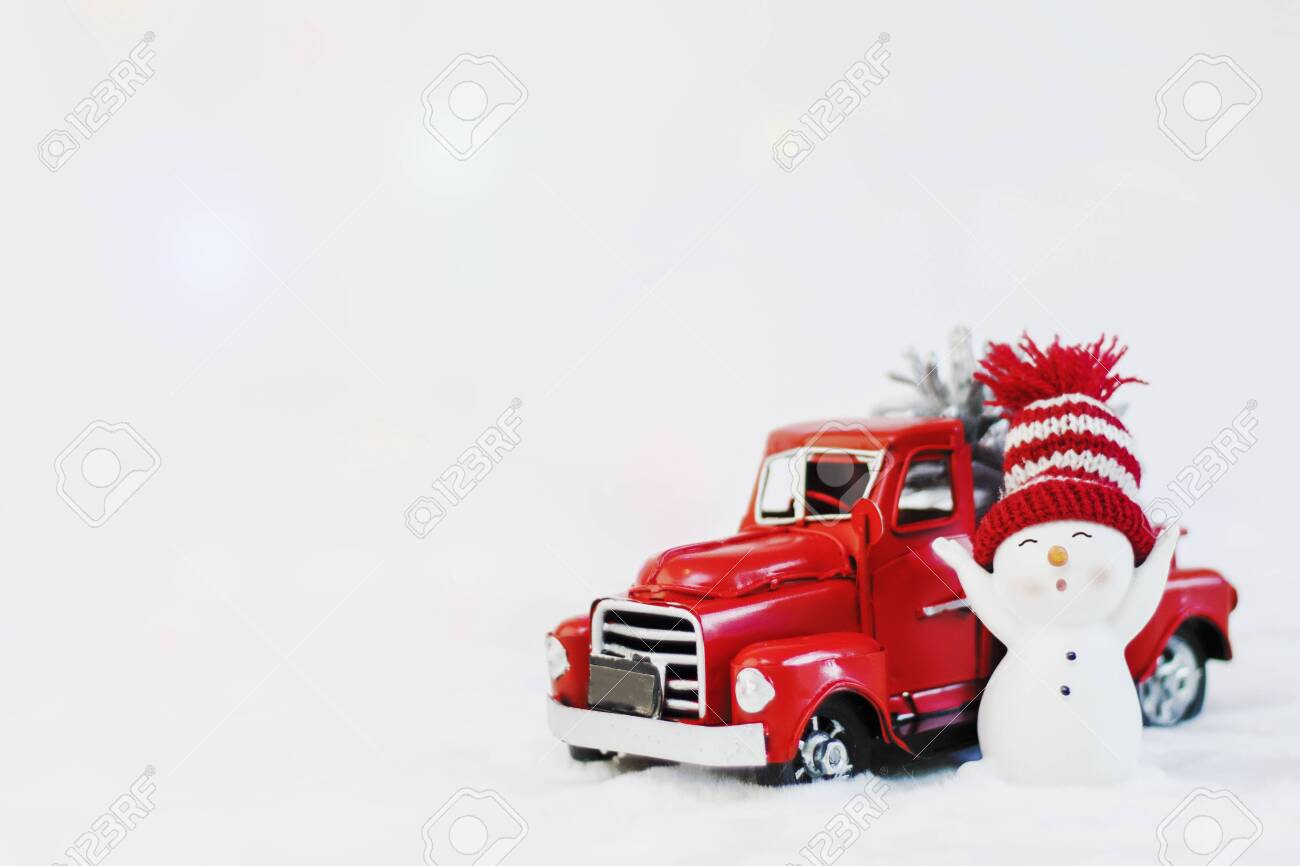 131217623 snowman in a red hat near red christmas truck pickup on a white background christmas pickup merry ch