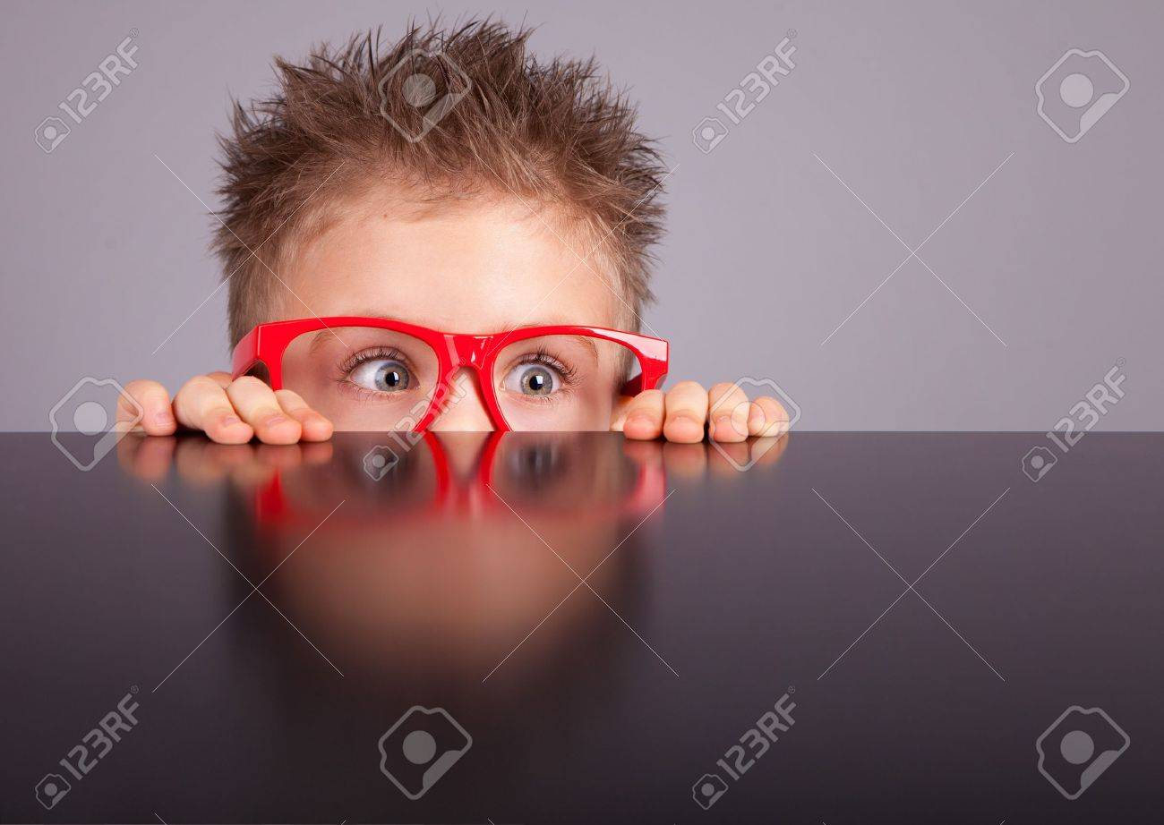 Five years old little cute boy hiding behind a table Stock Photo - 18057524