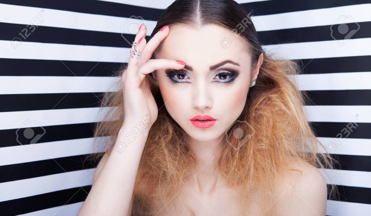 b43acb84f0a Portrait of beautiful young woman with professional party make up false  eyelashes on stripy background Stock