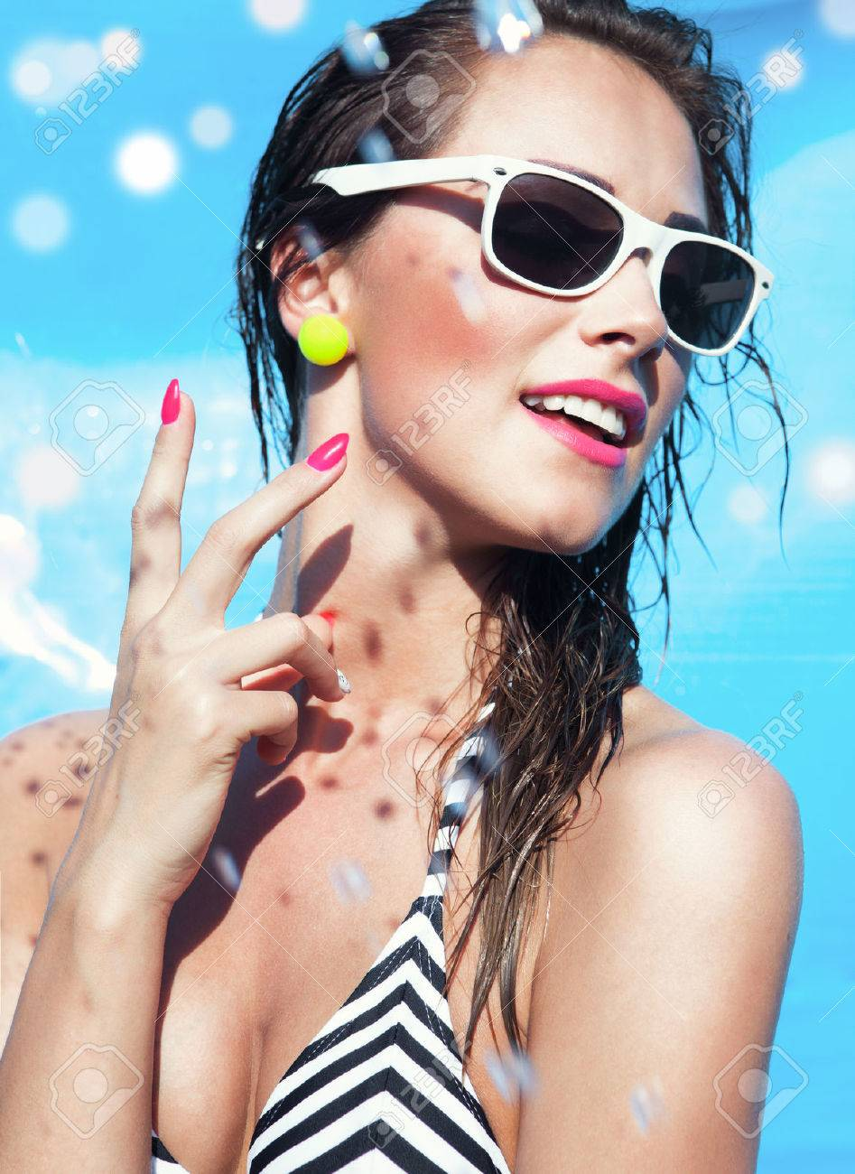 Colorful summer portrait of young attractive happy brunette woman wearing sunglasses at the swimming pool - 30302521