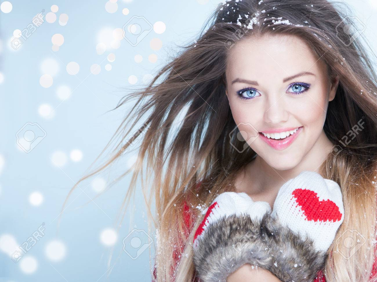 Beautiful happy young woman wearing winter gloves covered with snow flakes. Christmas portrait concept. - 45485636