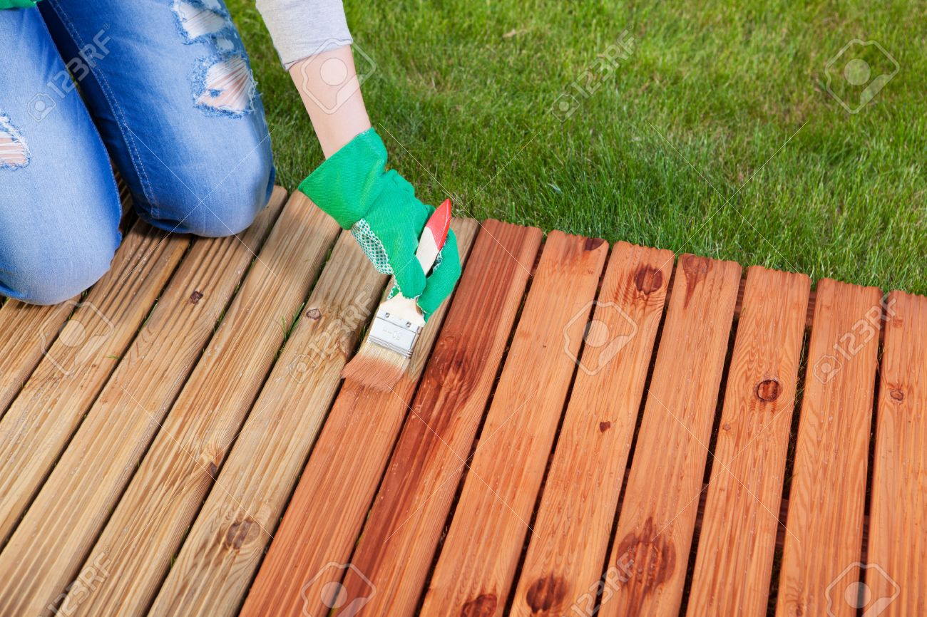 Applying Protective Varnish On A Patio Wooden Floor, Maintenance Concept  Stock Photo   43113267