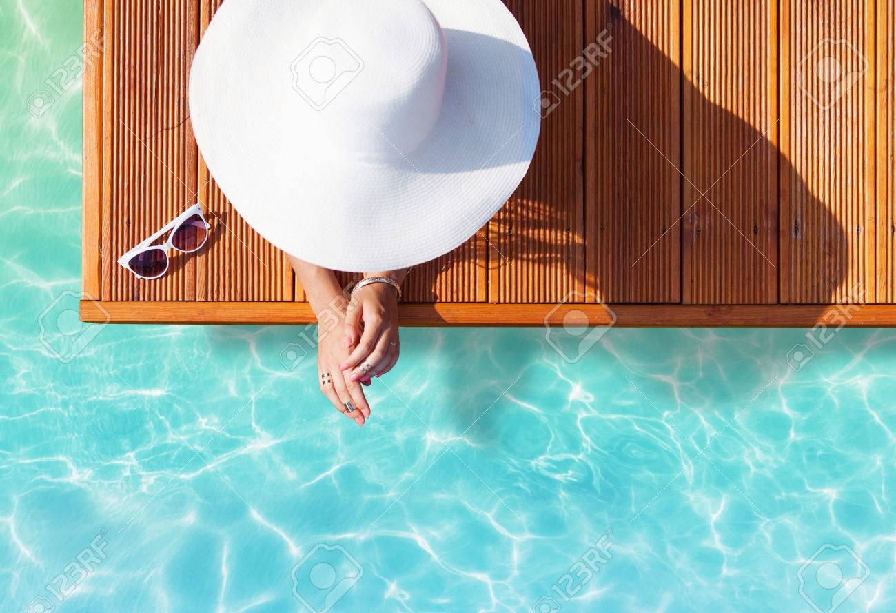 Summer holiday fashion concept - tanning woman wearing sun hat on a wooden pier view from above - 43113271