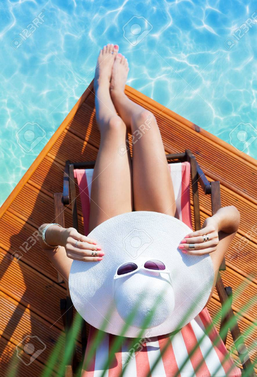 Summer holiday fashion concept - tanning woman wearing sun hat on a wooden beach chair at the pool view from above - 43113280