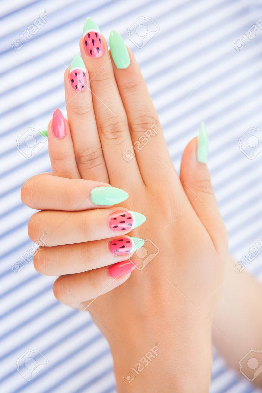 Hands close up of young woman with watermelon manicure summer nail art concept - 43150949
