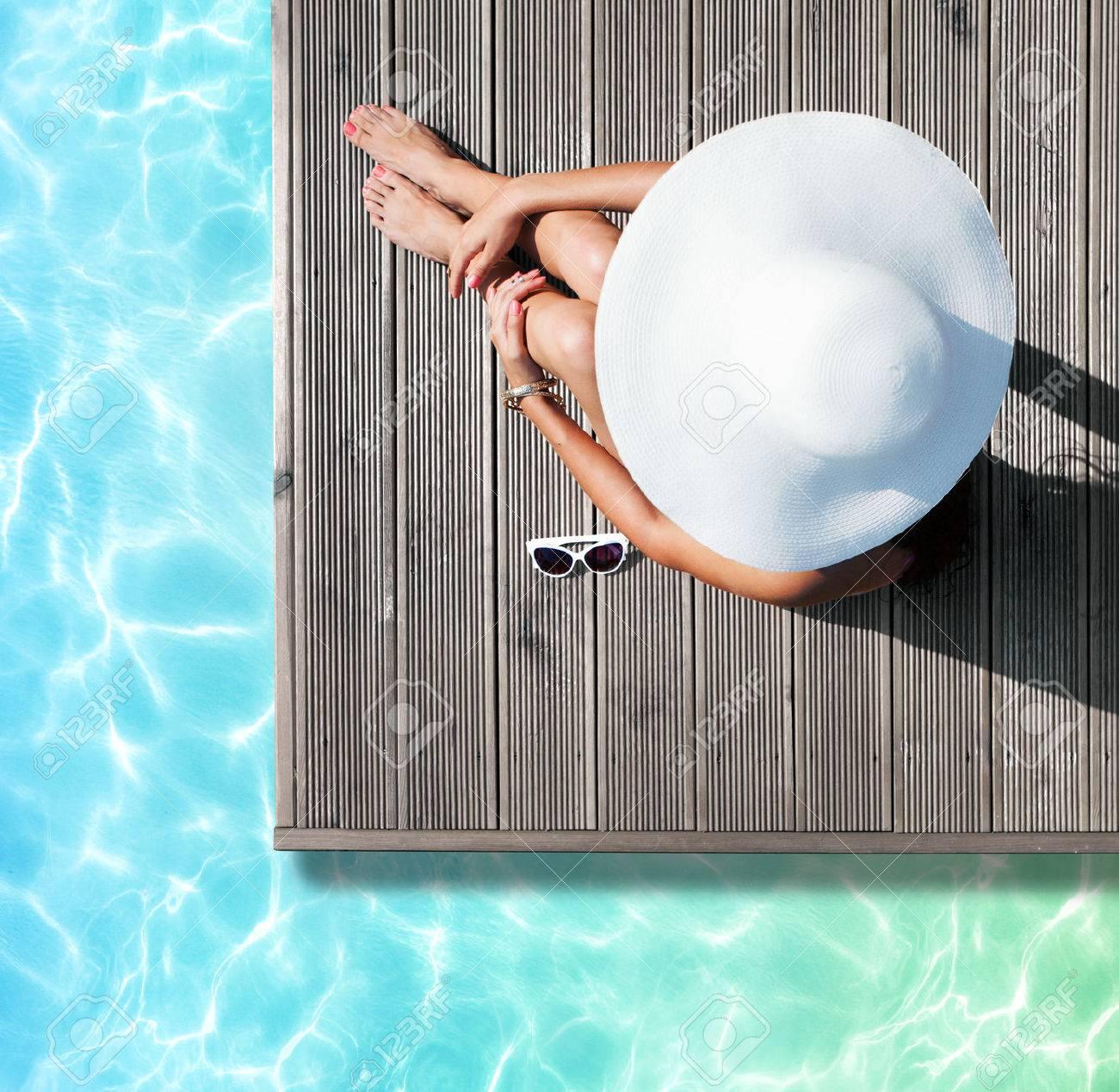 Summer holiday fashion concept - tanning woman wearing sun hat at the pool on a wooden pier view from above - 43150961