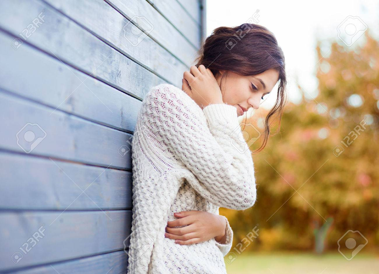 Beautiful natural young brunette woman wearing knitted sweater by the house. Fall and winter fashion concept. - 45215478