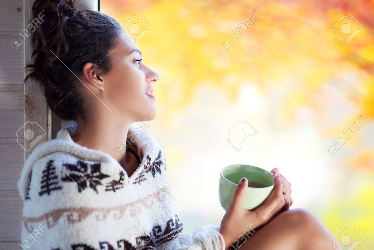Young Beaufort brunette smiling woman with cup of coffee wearing knitted nordic print poncho sitting home by the window. Blurred garden fall background. - 46287945