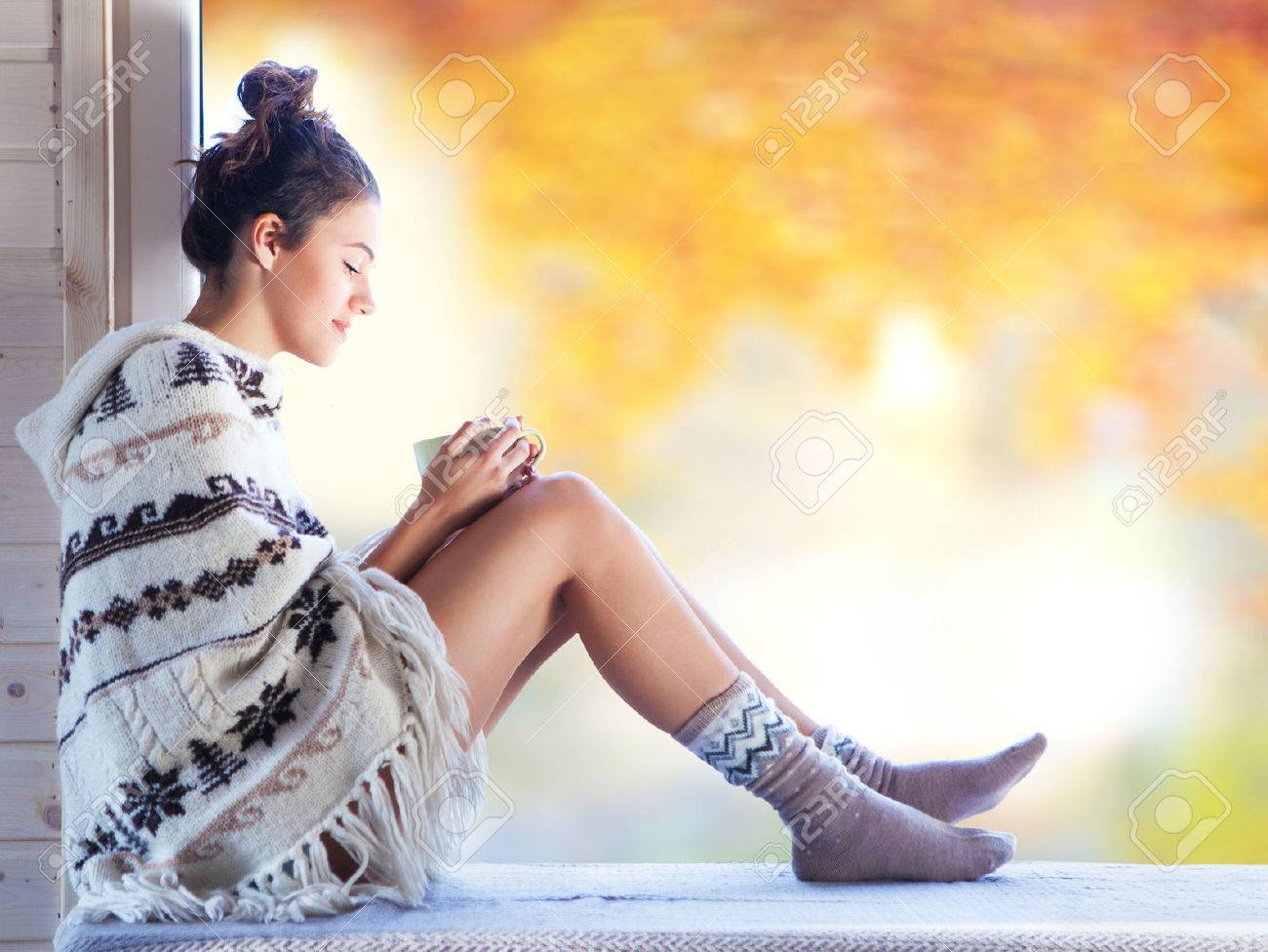 Young beautiful brunette smiling woman with cup of coffee wearing knitted nordic print poncho sitting home by the window. Blurred garden fall background. - 46287952