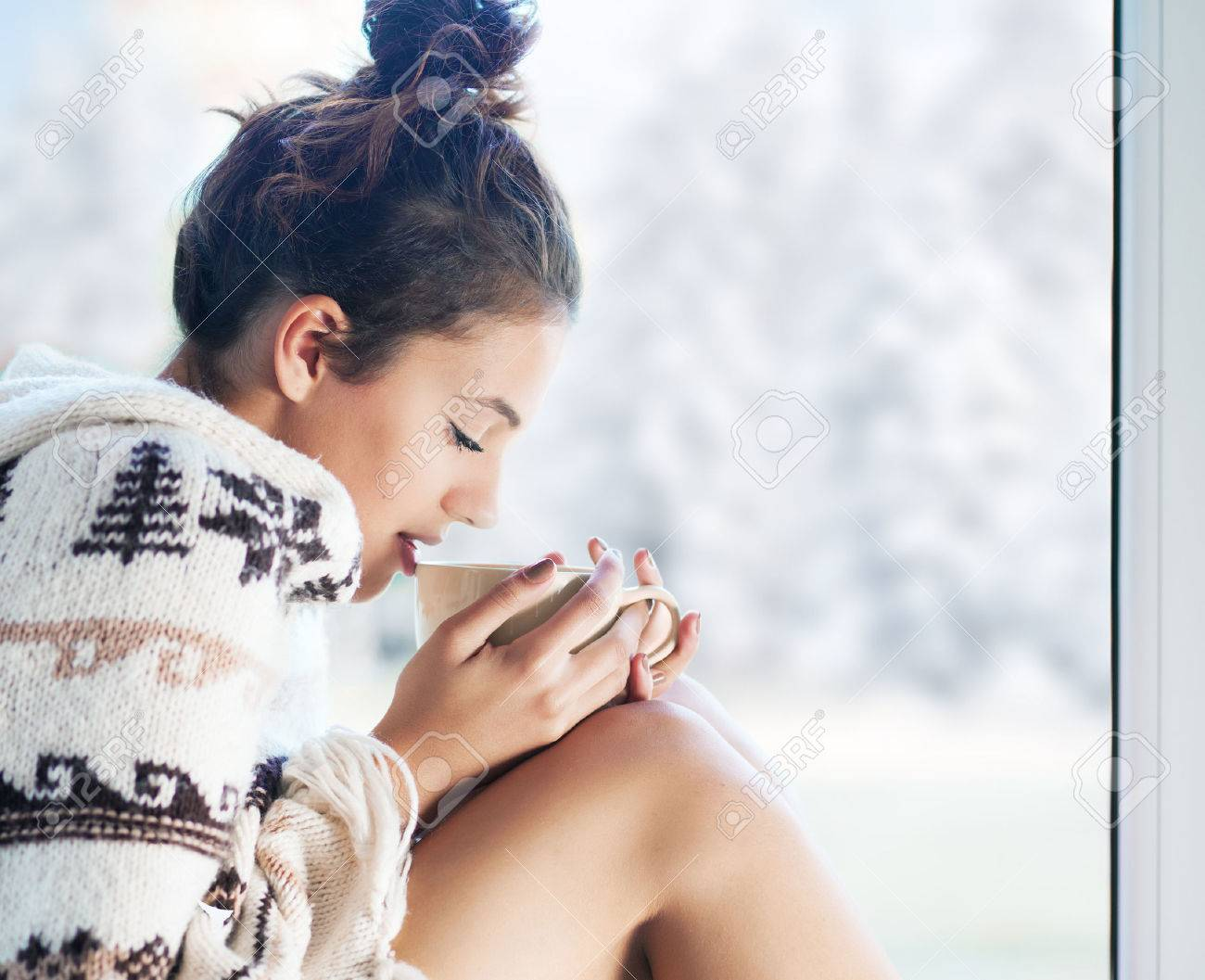 Young beautiful brunette woman drinking cup of coffee wearing knitted nordic print poncho sitting home by the window. Blurred winter snow tree background. - 46287955