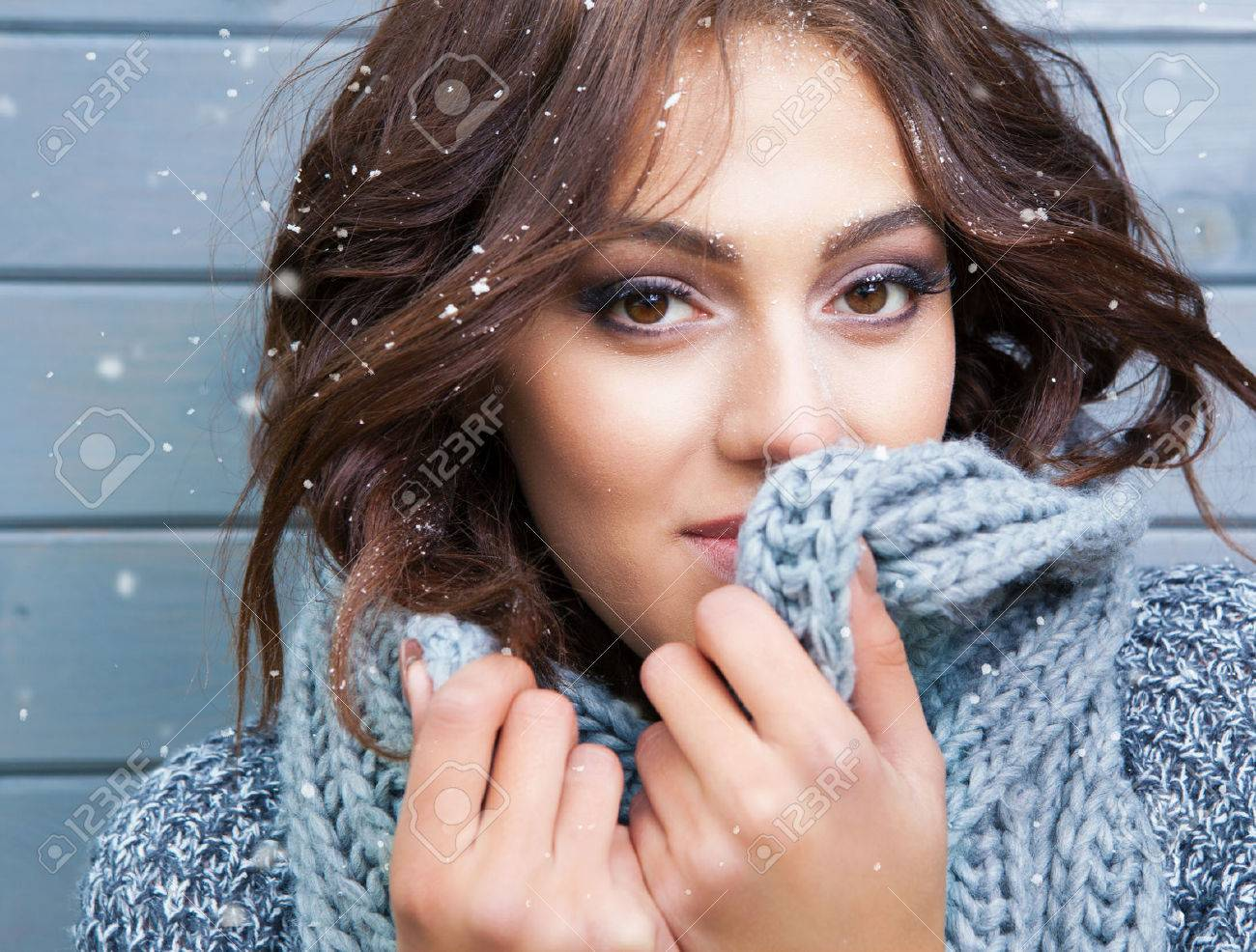 Beautiful natural looking young smiling brunette woman, wearing knitted scarf, covered with snow flakes. Snowing winter beauty concept - 48119299