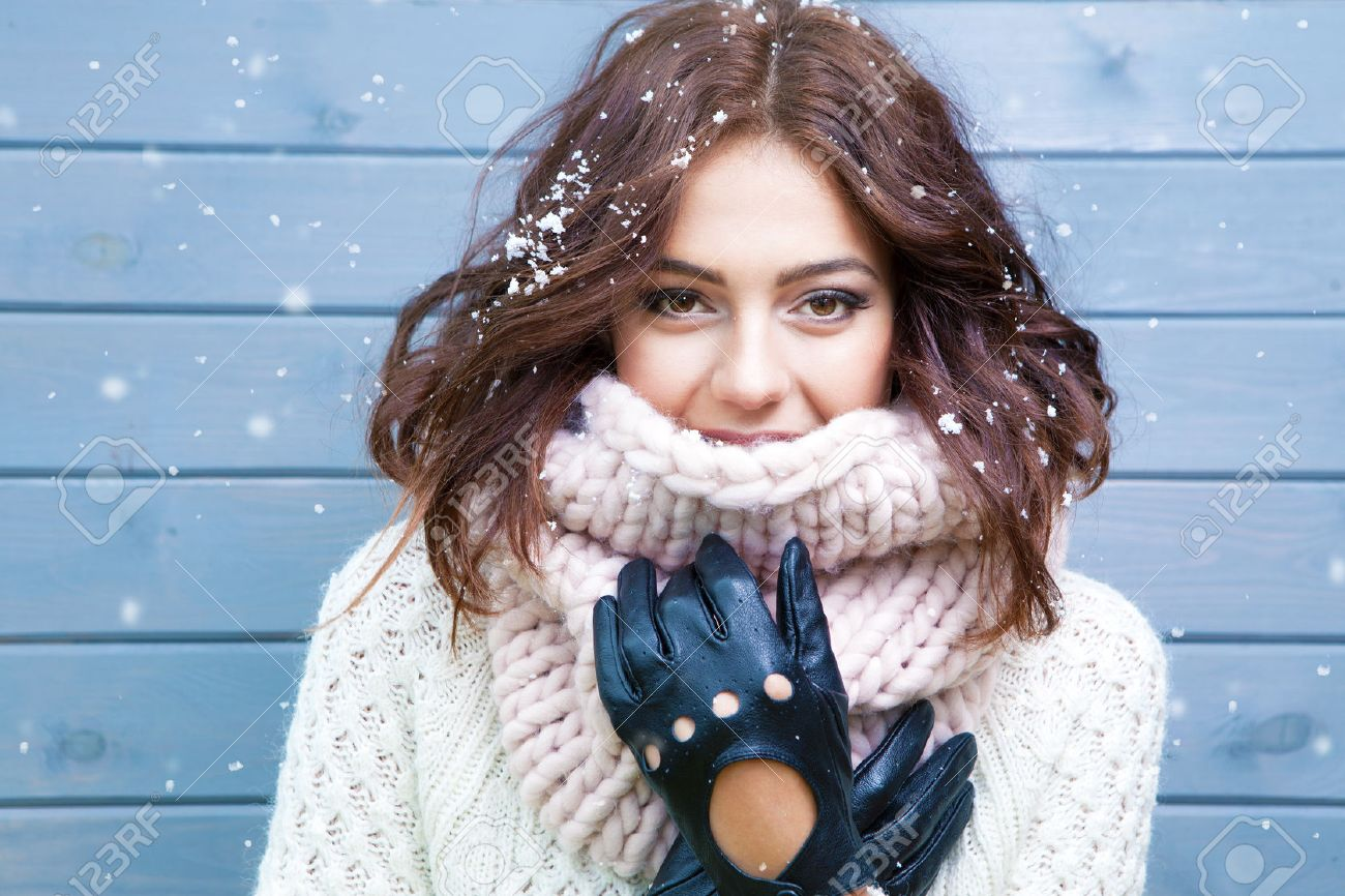 Winter portrait of young beautiful brunette woman wearing knitted snood covered in snow. Snowing winter beauty fashion concept. Stock Photo - 48119316