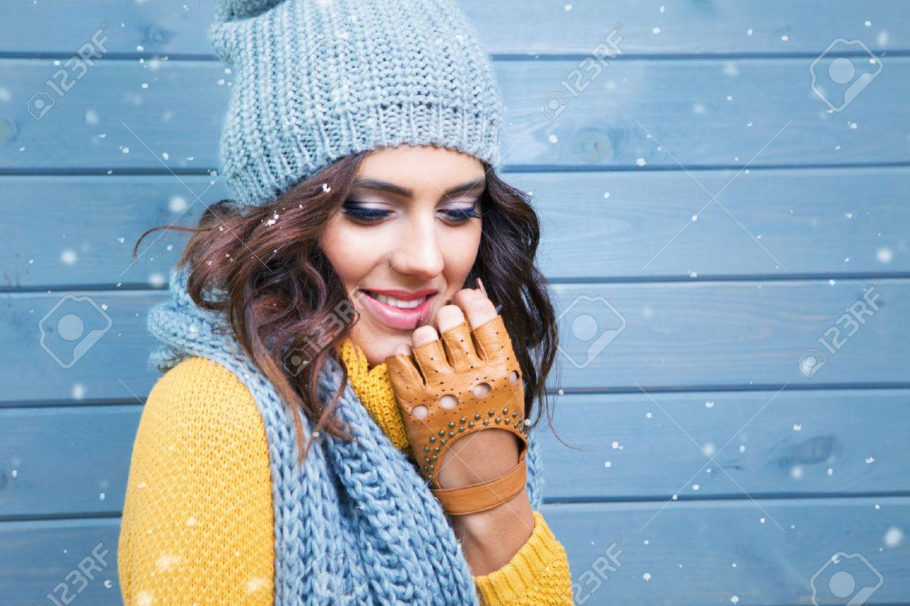 Beautiful natural young smiling brunette woman wearing knitted sweater, leather gloves, scarf and hat. Covered with snow flakes. Fall and winter fashion concept. - 48120114
