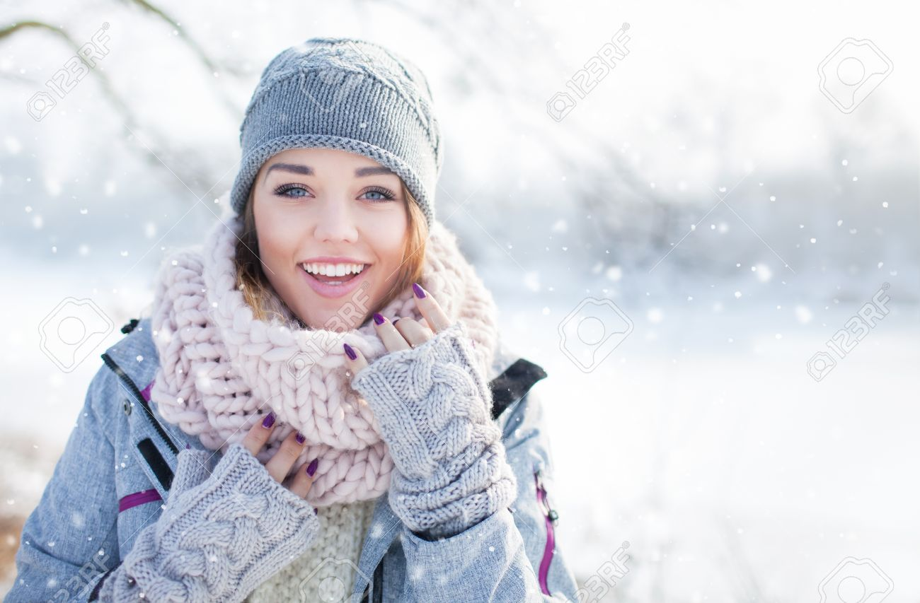Beautiful happy laughing young woman wearing winter hat gloves and scarf covered with snow flakes. Winter forest landscape background - 51250241