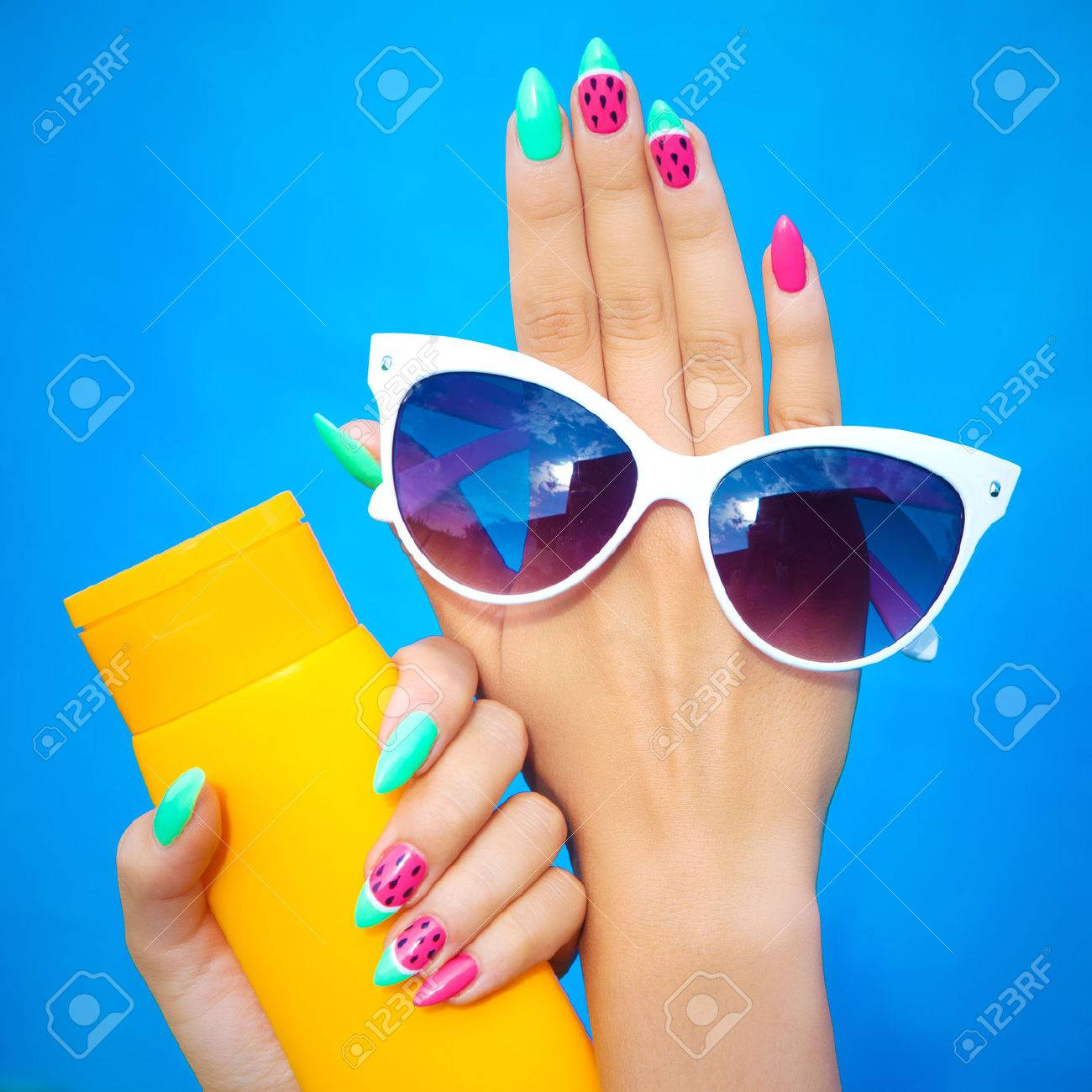 Summer fashion and beauty hand care concept, woman with watermelon gel nails holding sunglasses and sunscreen lotion - 56915008