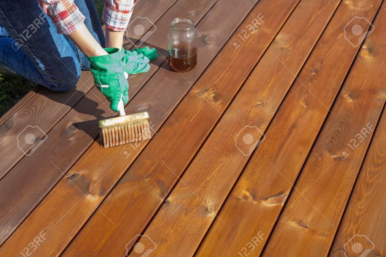 Holzfußboden Terrasse ~ Frau die schutzlack oder holzöl auf einer terrasse holzboden
