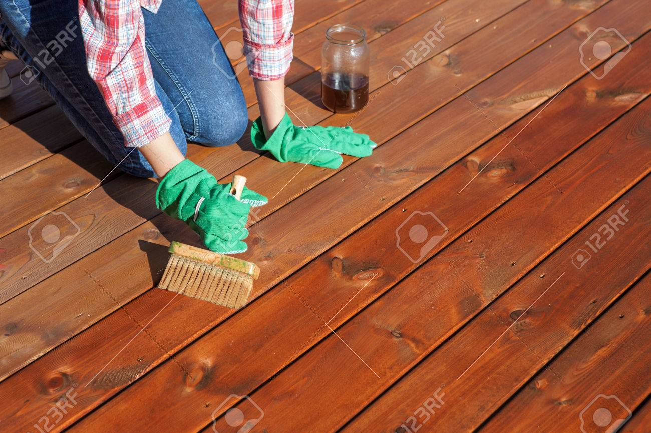 Woman applying protective varnish or wood oil on a patio wooden floor, house maintenance concept. Before and after effect - 56915029
