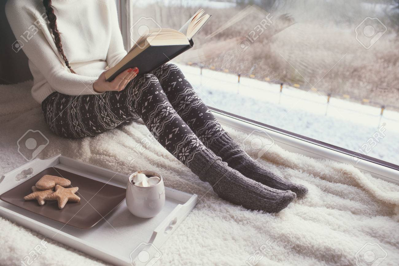 Young woman with cup of coffee and gingerbread is reading a book sitting home relaxing by the window. Snow winter home chill out concept. - 74409347
