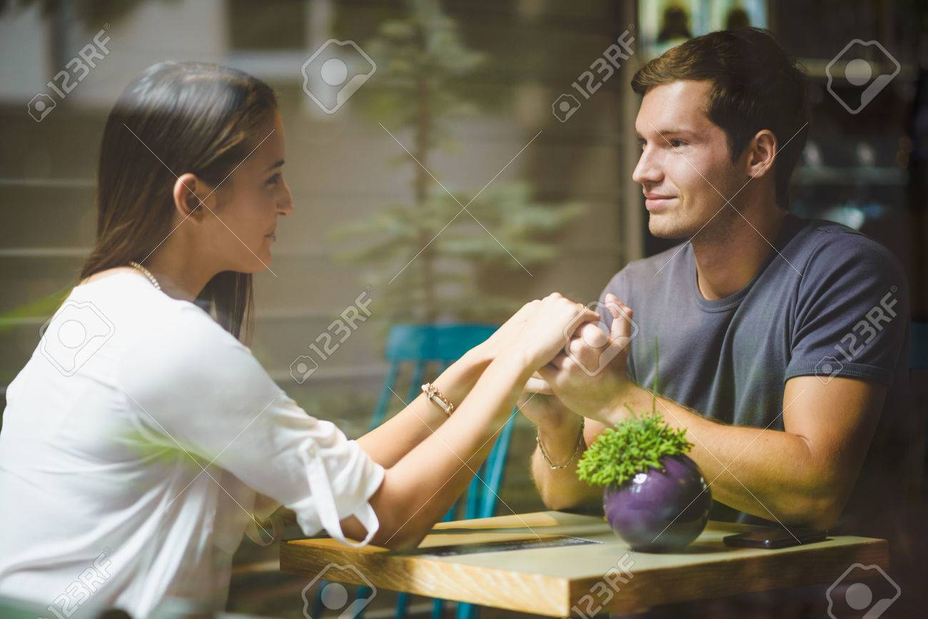 Young couple holding hands in cafe - 32277722