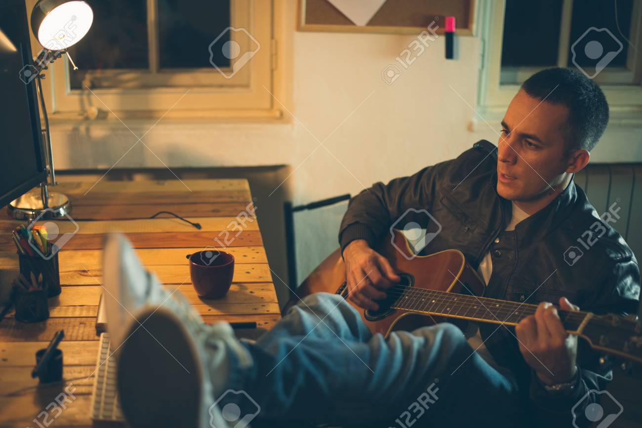 Man playing guitar at home after work - 35654186