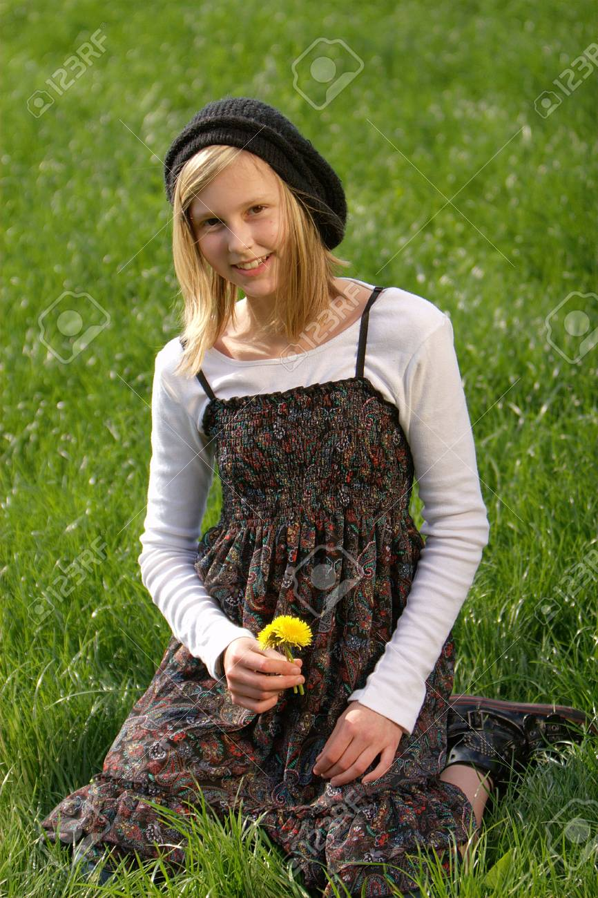blonde girl smiling and lies in the grass with a flower Stock Photo - 5214052