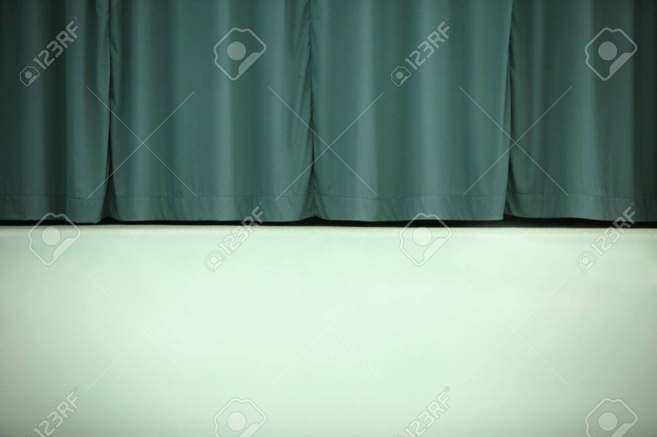 a dual color background image of a light green wall and dark green curtains stock photo