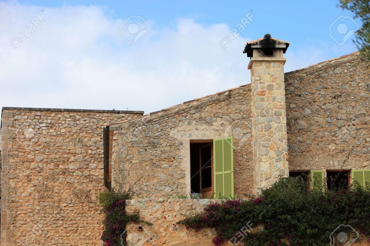 fachada exterior de un edificio de piedra con chimenea y ventanas con persianas verdes foto de